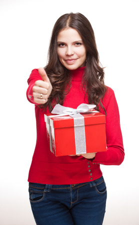 Portrait of a brunette christmas beauty holding shiny red gift box. photo