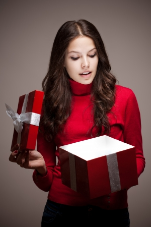Portrait of an attarctive young brunette woman opening red christmas gift box in mysterious lighting. photo