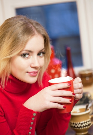 woman drinking coffee: Portrait of a cute blond girl with a cup of hot beverage  Stock Photo