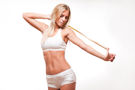 Portrait of fit slender young blond woman with measuring tape. Banco de Imagens