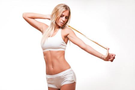 Portret van fit slanke jonge blonde vrouw met een meetlint.
