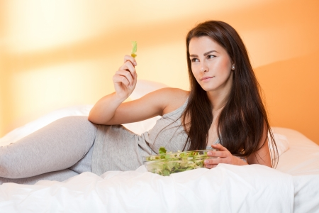 Gorgeous fit young brunette in bed with a bowl of fresh salad. photo