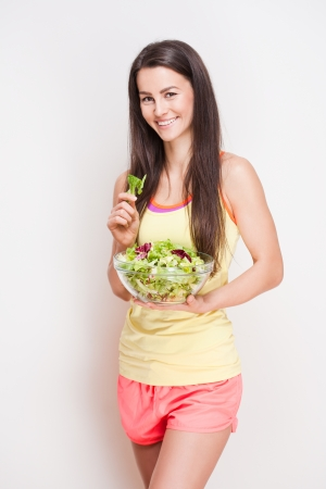 beautiful salad: Portrait of a fit young brunette woman having a healthy salad. Stock Photo