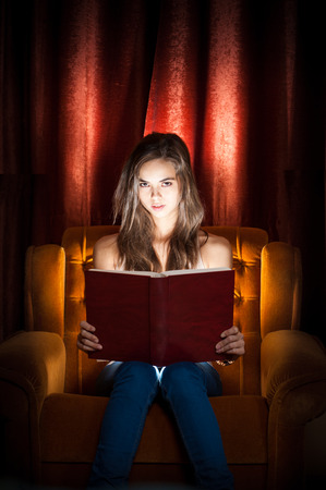 shocking: Portrait of expressive brunette beauty reading a book with creative lighting. Stock Photo