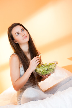 Beautiful young brunette woman eating bowl of salad in bed. photo