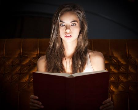suspenso: Conmocionado libro magnífico aspecto joven mujer morena lectura en la iluminación creativa.