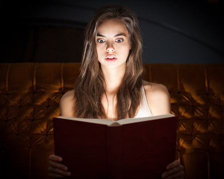 Gorgeous shocked looking young brunette woman reading book in creative lighting. Stock Photo