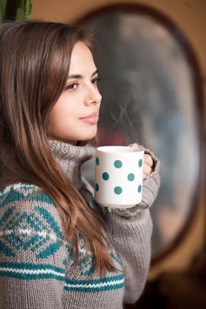 Portrait of a gorgeous brunette enjoying a cup of hot brunette. photo