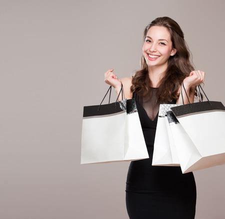 買い物袋との幸せな若いブルネットの美しさの肖像画。