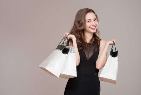 sexy black dress: Portrait of a happy young brunette beauty with shopping bags.