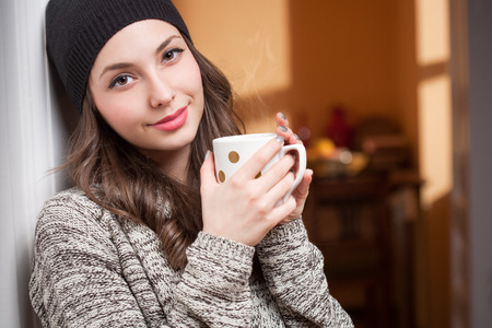 knit cap: Portrait of a gorgeous young bruette woman relaxing with mug of hot beverage.