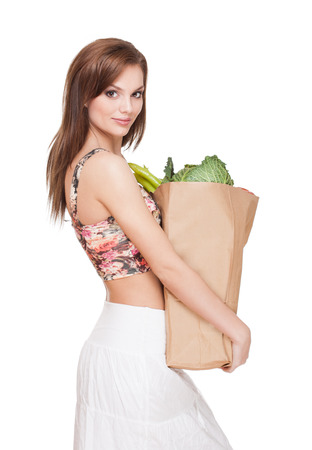 Portrait of a beautiful fit young woman with bag of fresh groceries. photo