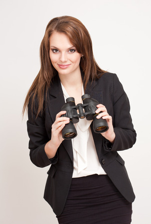 formal clothes: Brunette beauty in formal office clothes holding a binocular.