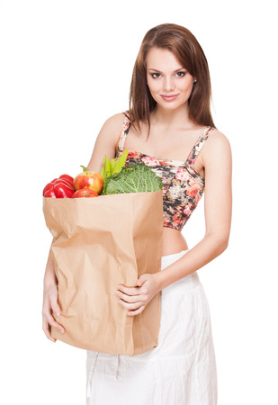 Gorgeous fit slender young brunette woman with bag of fresh vegetables. photo
