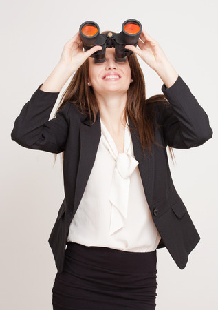 job searching: Portrait of a gorgeous young businesswoman using binoculars.