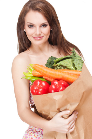 Pretty and healthy young brunette beauty holding bag of fresh vegetables. photo