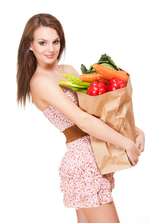 Gorgeous young brunette woman holding big bag of groceries. photo