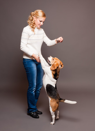 Portrait of a beautiful young blond woman with a cute beagle. photo