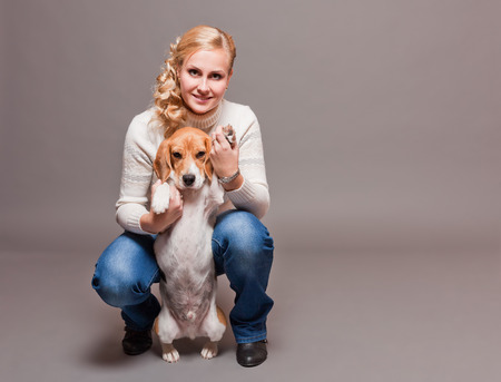 Portrait of a very cute trained beagle and his pretty owner. photo