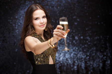 Portrait of a sensual beautiful young brunette woman holding a glass of champagne. photo