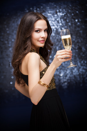 sexy birthday: Portrait of a sensual beautiful young brunette woman holding a glass of champagne.