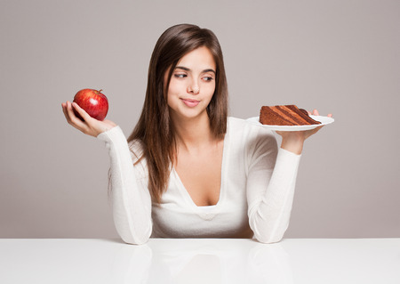Portrait of a gorgeous young brunette woman and food choices.