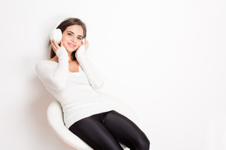 bar stool: Gorgeous dreamy young brunette woman wearing white headphones. Stock Photo