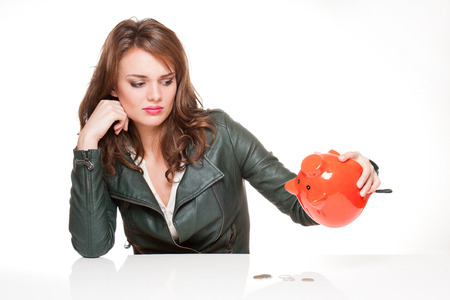 Gorgeous young brunette woman with orange piggy bank. photo
