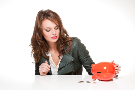Portrait of a cool beautiful young fashionable brunette with piggy bank. photo