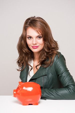 Beautiful young brunette woman with bright orange piggy bank. Stock Photo - 27779133