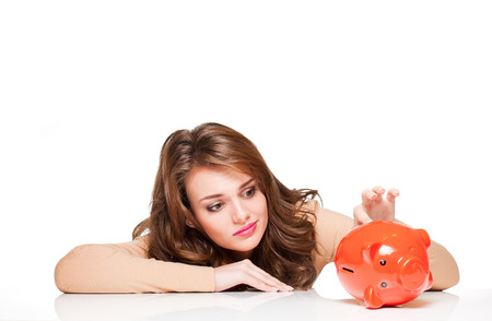 Portrait of expressive young brunette woman with her piggy bank. photo