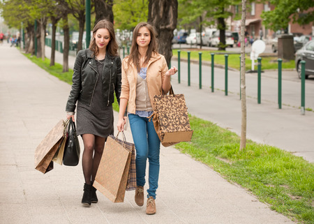 go shopping: Two beautiful happy young women go shopping in the city.  Stock Photo