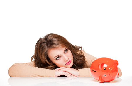 hoping: Beautiful young brunette woman with bright orange piggy bank.