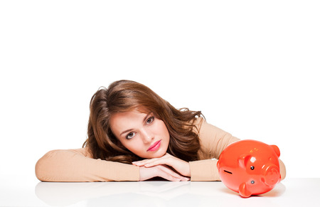 Beautiful young brunette woman with bright orange piggy bank. photo