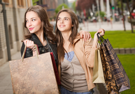 Two beautiful happy young women go shopping in the city.  photo