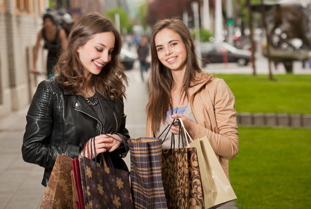 Couple of gorgeous young brunette women with shopping bags outdoors. photo