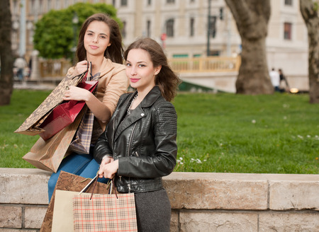 Two beautiful happy young women go shopping in the city   photo