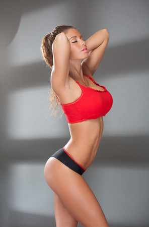 Portrait of a super fit sexy young brunette woman. photo