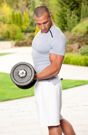 triceps: Outdoors portrait of a muscular tanned lean young man.
