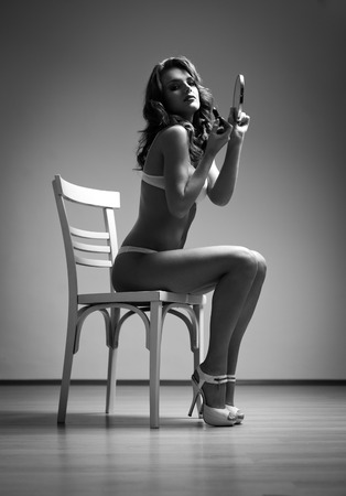 Dramatic art photo of a gorgeous slender young brunette woman in lingerie.