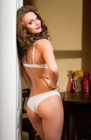 Portrait of a beautiful young brunette woman wearing elegant white lingerie. Stock Photo