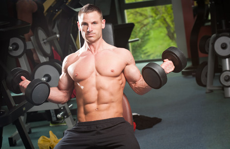 six persons: Attractive very fit young man working out in a gym. Stock Photo