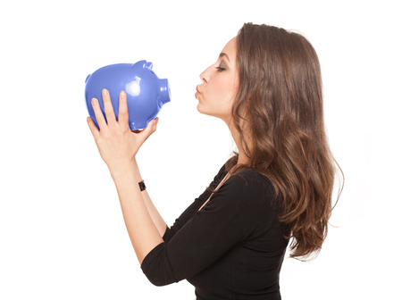 Portrait of a gorgeous young brunette woman with shiny piggy bank. photo