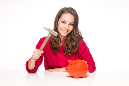 Portrait of a beautiful young brunette woman with colorful piggy bank. photo