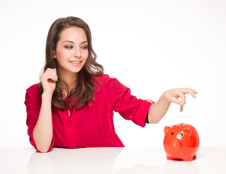 Portrait of a beautiful young brunette woman with colorful piggy bank. Stock Photo - 28403132