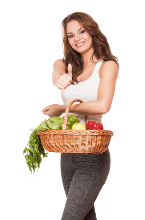 Gorgeous young brunette woman with a basket of fruits and vegetables. photo