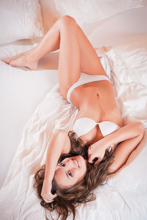Portrait of a gorgeous sensual happy young brunette woman wearing lingerie in bed. photo