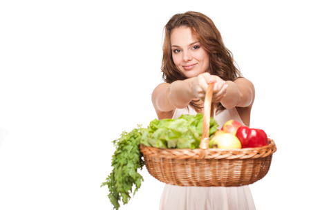 Gorgeous young brunette woman with basket of fresh produce isolated on white background. photo