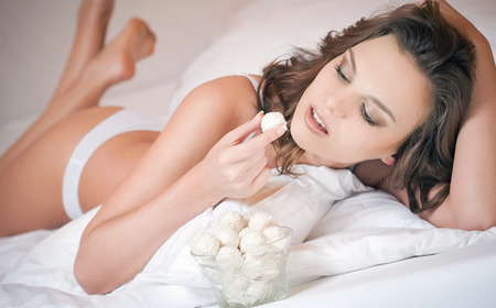 Portrait of a gorgeous young brunette woman in lingerie having pralines in bed. photo