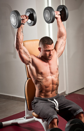 pectoral: Portrait of a strong fit young man exercising in a gym.